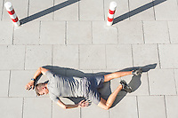 High angle view of tired sporty man lying on sidewalk