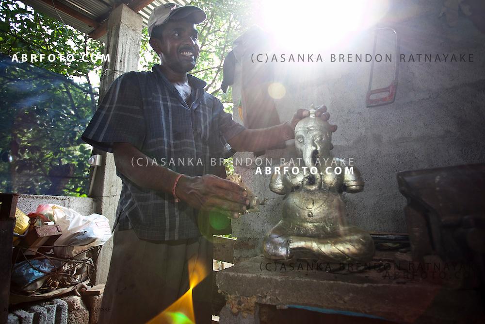 Craftsmen showing his unpolished brass statue of the hindu god Ganesha