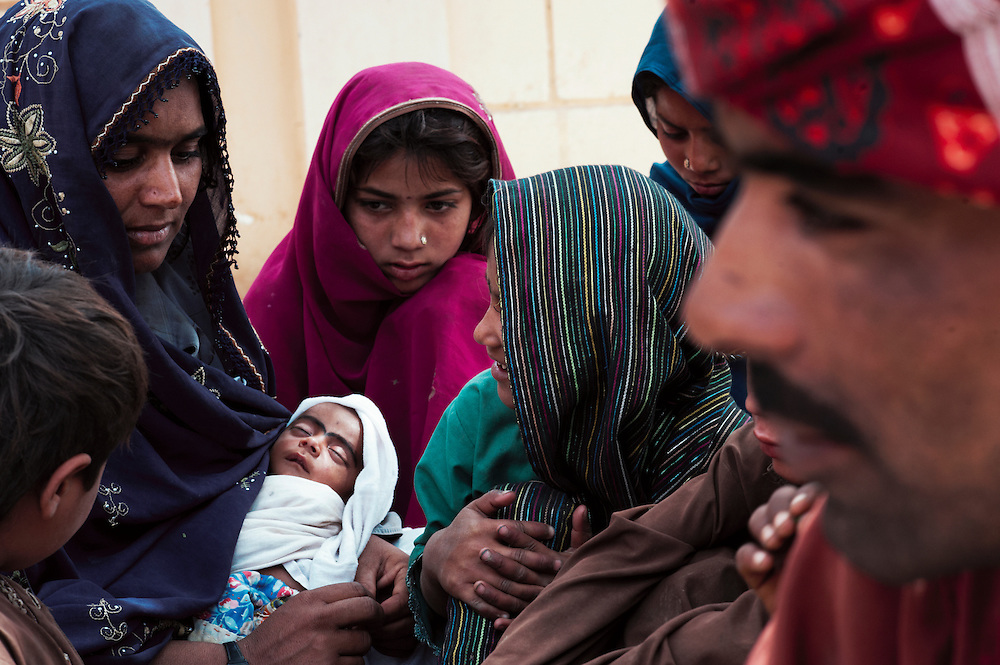Abdul Razak, a muslim who converted from hindu 12 years earlier sits with his family at Bharchundi Sharif, a Muslim shrine in Ghotki district, Sindh, Pakistan on March 23, 2012.A rise in in reports of forced conversion of Hindu girls to Islam in provinces in Pakistan has gained prominence within the political, media, religious and social domains with the case of a 21 year old woman Rinkle Kumari. On February 24, 2012 her family reported to police of Ghotki district, Sindh province that she had been abducted by armed men from the family home in the village of Mirpur Mathelo. it is then alleged by the family and broadrer hindu community that she was forced to convert to Islam and marry Syed Naveed Shah, a neighbour of the girl within their village. Complications with court hearings for the case, perceptions by the Muslim community that the police sided with the Muslim community when dealing with issue and the politicisation of the case by a Pakistan Peoples Party Member for National Assembly Mian Abdul Haq alias Mian Mitho has led to a hearing being called in the Supreme Court, Islamabad, Pakistan on March 26, 2012. The hearing will hopefully ascertain whether the girl was abducted or in fact left with Syed Naveed Shah of her own free will.