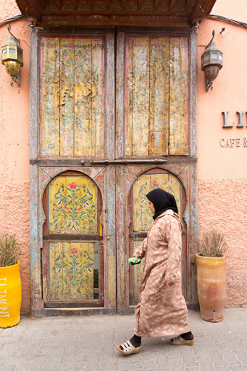 MARRAKESH, MOROCCO - 19TH APRIL 2016 - Lady wearing traditional Moroccan clothing and headscarf walks past a colourful, old wooden doorway in the Marrakesh old medina, Morocco.