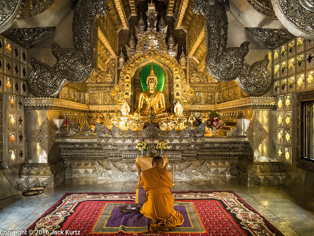 "03 APRIL 2016 - CHIANG MAI, THAILAND: A Buddhist monk prays in the ordination hall of Wat Sri Suphan. Wat Sri Suphan is also known as the ""Silver Temple"" because of its silver ubosot, or ordination hall. The temple is more than 500 years old but the silver ordination hall was recently remodeled. The ordination hall is covered in silver and the interior is completely done in silver and gold. It's traditionally served as the main temple for the silversmiths of Chiang Mai, whose community is around the temple.     PHOTO BY JACK KURTZ"
