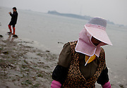 "Portrait of a woman with her head covered at the open ""Mysterious Sea Road"" in Hoedong shore (Jindo island). Jindo is the 3rd biggest island in South Korea located in the South-West end of the country and famous for the ""Mysterious Sea Route"" or ""Moses Miracle"". Every spring thousands flock to the shores of Jindo to walk the mysterious route that stretches roughly three kilometers from Hoedong to the distant island of Modo. Materializing from the rise and fall of the tides, the divide can reach as wide as forty meters."