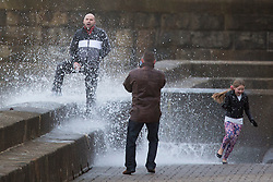 "© Licensed to London News Pictures. 09/11/2015. Bridlington, UK. FRAME 7 OF 9. A man poses for a photograph on the sea defences at the sea side town of Bridlington & gets caught out by a huge wave. The Yorkshire region was hit by severe gales this afternoon with winds up to 60mph. The Met Office warned West Yorkshire to expect gales and locally severe gales over high ground, with some ""very gusty"" winds to the east of high ground as well.<br /> Photo credit: Andrew McCaren/LNP"