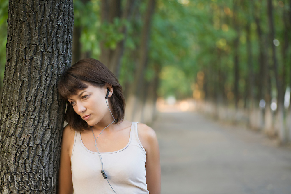 Woman listens to personal stereo in public park