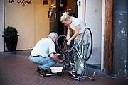 Een man helpt een meisje met het plakken van de acherband van haar fiets.<br /> <br /> A man is assisting a young woman with repairing the tyre of her bike.