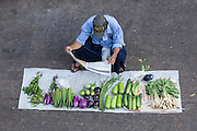 Man reading newspaper, selling vegetables at Scott Market, Yangon