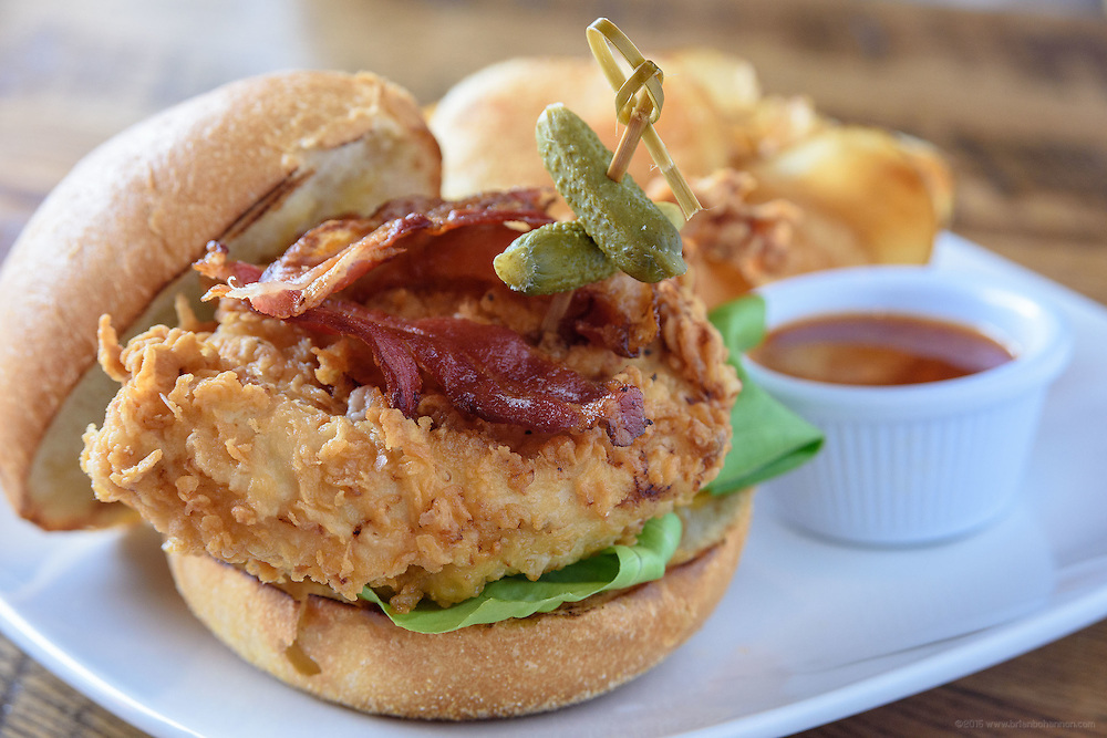 The Fried Chicken Sandwich on a brioche bun with pickle, sweet chili sauce, cheddar, carmelized onion and bacon and served with house-made chips at Somewhere restaurant at 1135 Bardstown Road, next to Nowhere bar. July 26, 2016