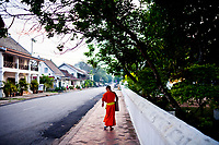 A novice monk walking to his studies along the quiet roads of Luang Prabang at dusk.