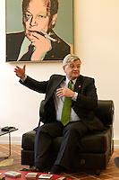 28 APR 2004, BERLIN/GERMANY:<br /> Joschka Fischer, B90/Gruene, Bundesaussenminister, sitzt waehrend einem Interview unter einem Bild von Willy Brandt, in seinem Buero, Auswaertiges Amt<br /> Joschka Fischer, Green Party, Federal Minister of Foreign Affairs, during an interview, in his office<br /> IMAGE: 20040428-03-030