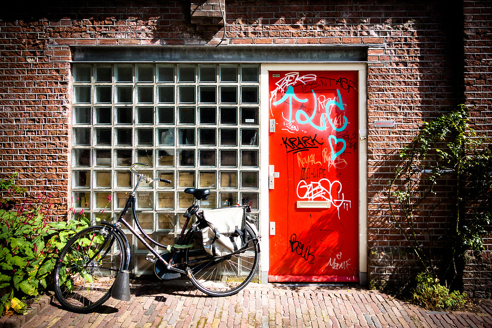 A typical Amsterdam scene: brick, a door, a bicycle and some graffiti.