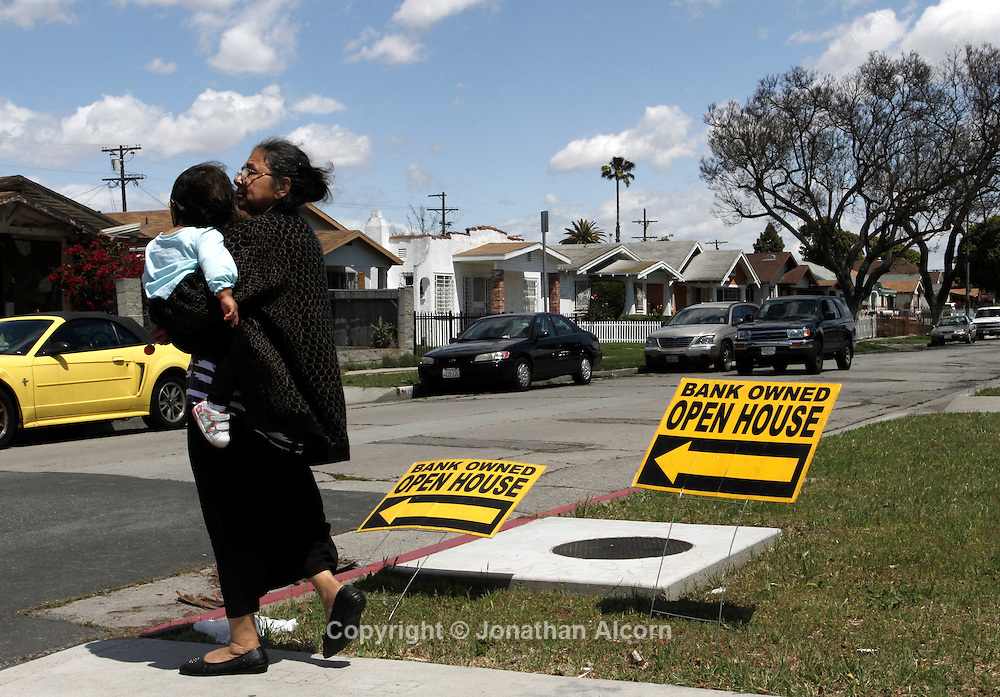 A woman holding a child walks past open house signs on West 73rd Street, a street in the vicinity  Florence Ave in Los Angeles, California, April 14, 2012.  on Florence Ave in Los Angeles, California, April 15, 2012.the infamous intersection of Florence and Normandie in Los Angeles, California, April 5, 2012. This April 29 will be the 20 year anniversary of the flashpoint of the Los Angeles Riots in the area of Florence and Normandie in South Los Angeles. ©Jonathan Alcorn/JTA