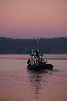 A tugboat leaves it's berth in Campbell River enroute through Discovery Passage to pick up its tow as twilight sets in.  Campbell River, Vancouver Island, British Columbia, Canada.