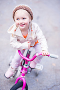 Young girl in stylish clothing on her pink bicycle