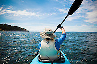 A rear view of a woman paddling in a kayak on the Haro Straight off San Juan Island, WA, USA.