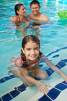 Girl with parents in swimming pool, portrait