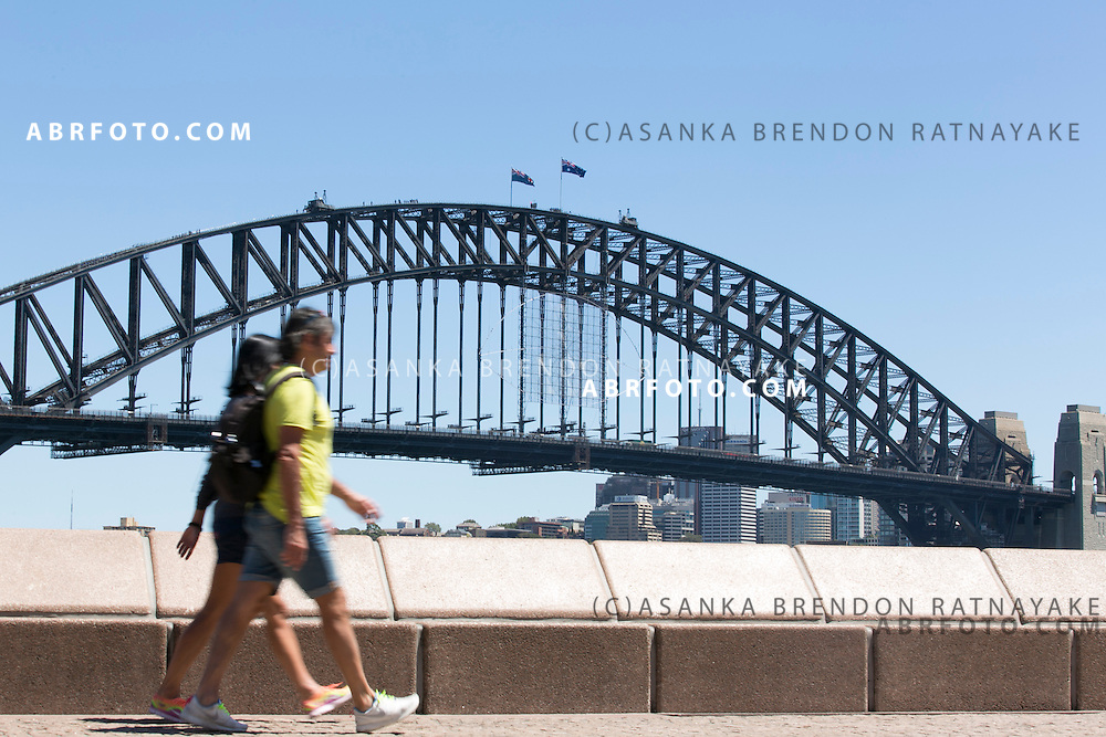 Tourists walk past the Sydney Harbour Bridge viewed from Circular Quay