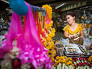 29 JUNE 2015 - BANGKOK, THAILAND:  A woman making and selling marigold garlands in the Bang Chak Market in Bangkok. The Bang Chak Market serves the community around Sois 91-97 on Sukhumvit Road in the Bangkok suburbs. About half of the market has been torn down, vendors in the remaining part of the market said they expect to be evicted by the end of the year. The old market, and many of the small working class shophouses and apartments near the market are being being torn down. People who live in the area said condominiums are being built on the land.    PHOTO BY JACK KURTZ
