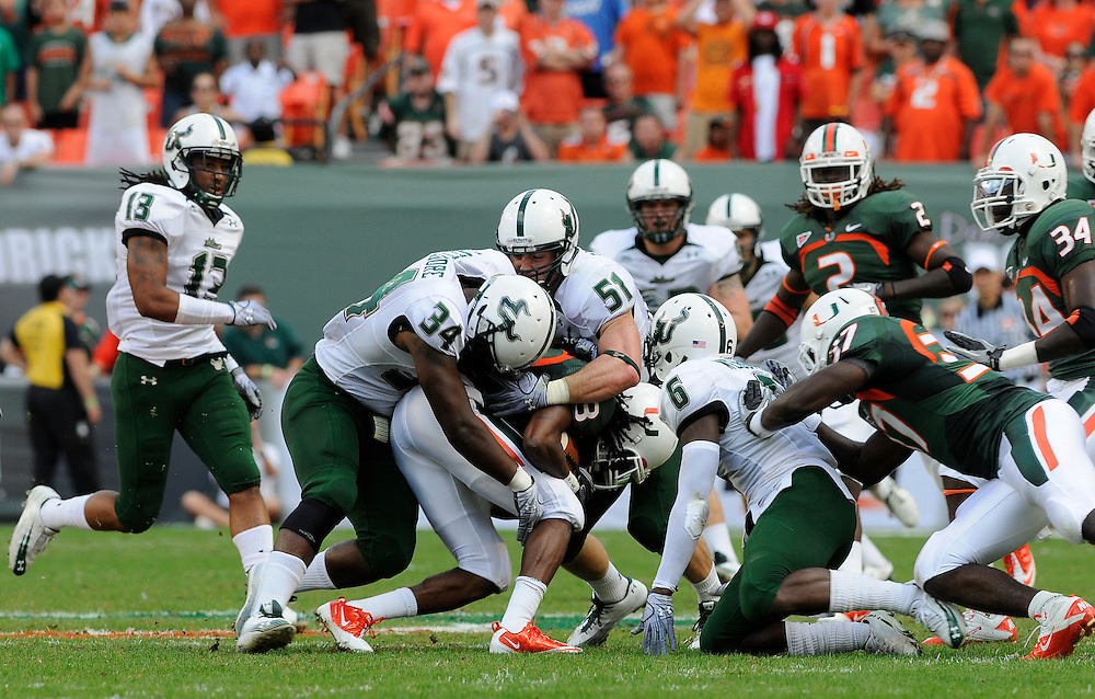 MIAMI GARDENS, FL - NOVEMBER 27: DeDe Lattimore #34 and Ammando Sanchez #51 tackles Travis Benjamin #3 of the Miami Hurricanes during the game against the Miami Hurricanes at Sun Life Stadium in Miami Gardens, Florida on November 27, 2010. South Florida defeated the Hurricanes 23-20.