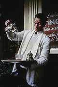 AFRICA; MOROCCO; TANGIER:  Formal waiter pouring Moroccan tea with a flourish.