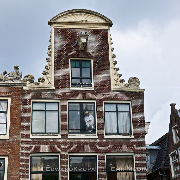 An interesting display of a hanging man in the window of an ornate old building in the heart of Amsterdam.