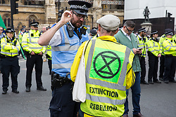 London, UK. 23rd April 2019. A climate change activist from Extinction Rebellion speaks to a police liaison officer in front of a police cordon in Parliament Square positioned to prevent fellow activists from Extinction Rebellion from attempting to deliver letters to Members of Parliament requesting meetings to discuss the issue of climate change.