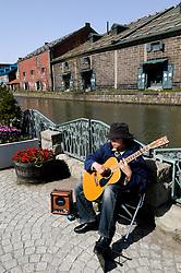 Musician playing guitar along canal in historic Otaru on Hakkaido Island in Japan