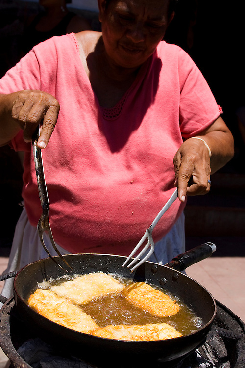 A woman cooking at a street stall. She is cooking fried cheese bubbling and cooking in a pan on the side walk in Granada, Nicaragua