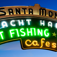 "Santa Monica Pier sign panorama picture at dusk.  Panorama picture ratio is 1:3. The famous Santa Monica pier neon sign says ""Santa Monica Yacht Harbor Sport Fishing Boating Cafes"". Santa Monica Pier is a landmark located in Los Angeles County Southern California and has an amusement park with a ferris wheel, roller coaster, restaurants, and other attractions."