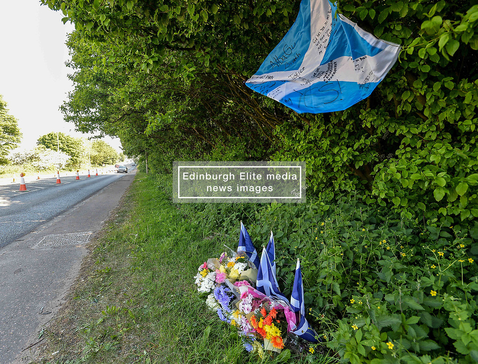 Family and friends of the driver who died after his vehicle was involved in a horror accident early on Saturday morning after a stolen car went on the wrong side of the road have laid flowers and Scottish flags at the scene.<br /> <br /> © Dave Johnston / EEm
