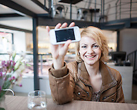 Portrait of smiling young woman displaying cell phone in cafe