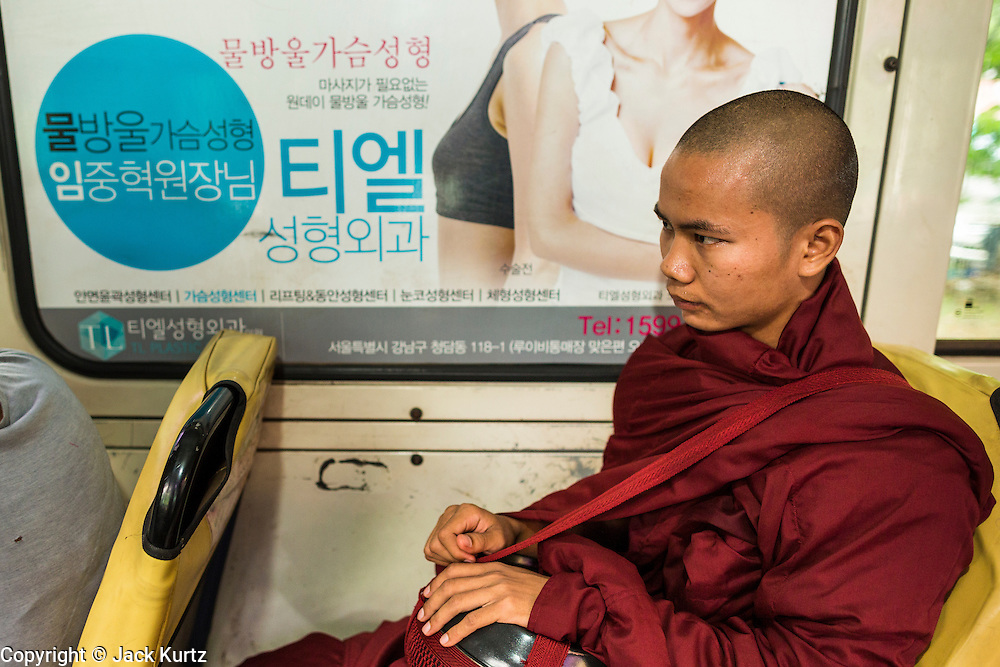 19 JUNE 2013 - YANGON, MYANMAR:  A Buddhist monk on a Yangon bus. Yangon buses are generally overcrowded and in poor repair but as the economy improves newer, but still used, Japanese and Korean buses are being imported. Hundreds of bus routes criss-cross Yangon, providing the cheapest way of getting around the city. Most fares are less than the equivalent of .20¢ US.  PHOTO BY JACK KURTZ