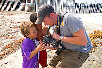 Photographer, Brian Auer Showing Mexican Kids Pictures on Digital Camera, Border Field State Park, California, USA