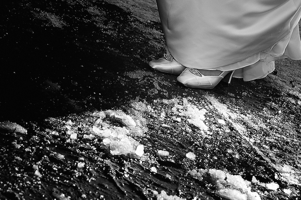 A bride wears her wedding shoes on icy pavement.