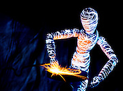 Glowing mannequin holding metal against a grind stone as it makes sparks.Black light