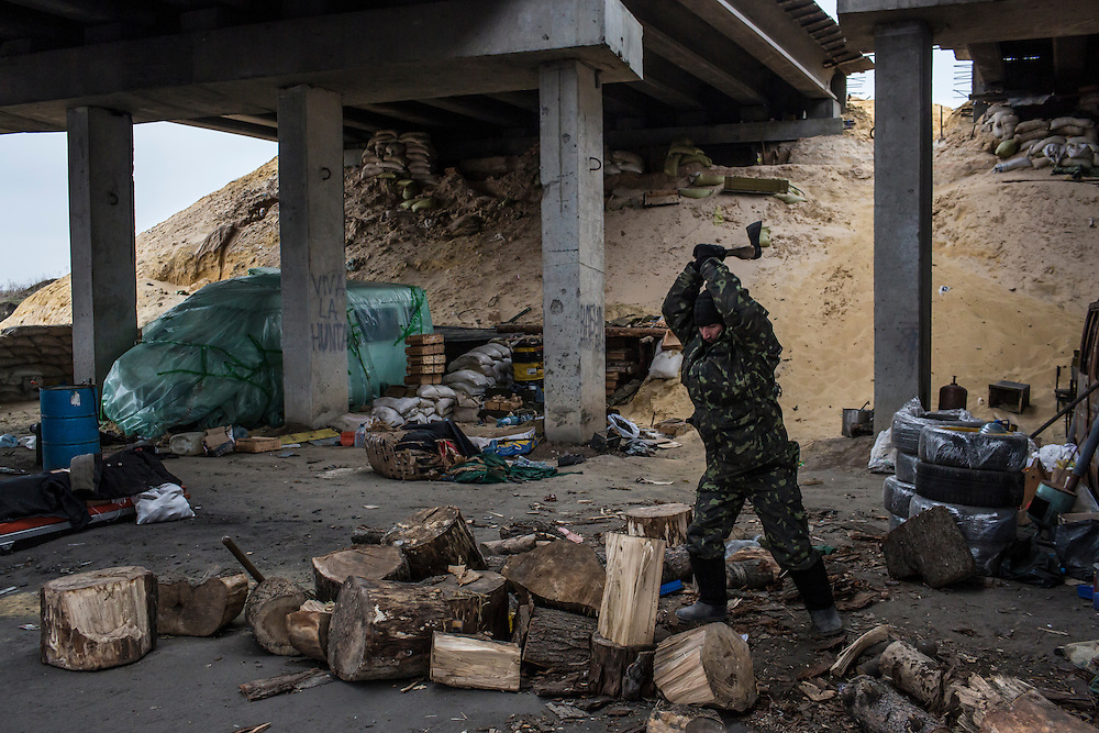 PERVOMAISKE, UKRAINE - NOVEMBER 18, 2014: Yura, a member of the 5th platoon of the Dnipro-1 brigade, a pro-Ukraine militia, chops fire wood at their post underneath a bridge in Pervomaiske, Ukraine. CREDIT: Brendan Hoffman for The New York Times