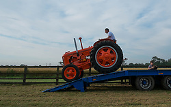 © Licensed to London News Pictures. <br /> 29/07/2014. <br /> <br /> Kirkbymoorside, United Kingdom<br /> <br /> A man drives his tractor off a trailer at the Ryedale agricultural show in North Yorkshire. The show was established in 1855 and is a traditional agricultural show renowned for its high standards of entries into the numerous livestock categories.<br /> <br /> Photo credit : Ian Forsyth/LNP