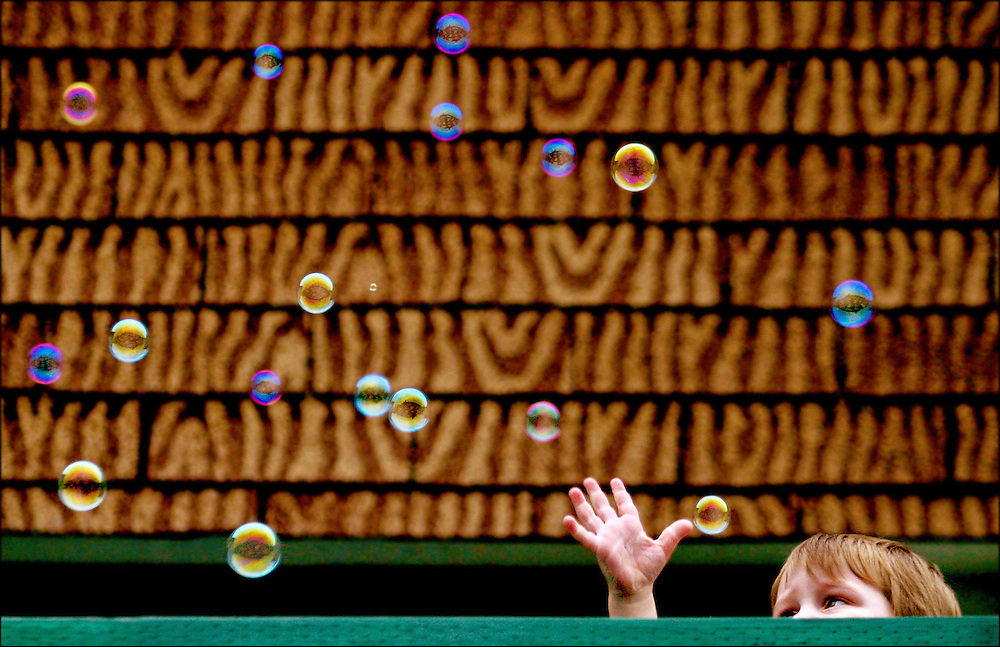 Two-year-old Jareth Fellroth attempts to catch bubbles blown by his mother, Angela Fellroth, while the two played on their deck at Hillside Manor apartments in Everett, Wash. The two were watching other tenants protest in the parking lot below, siting poor living conditions, and a drugridden community.