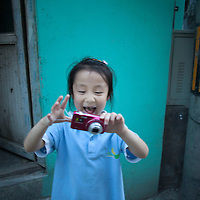 BEIJING, JULY,12-14,2013 : xx, die juengste Teilnehmerin des Fotoworkshops, fotografiert in ihrer Nachbarschaft nach der Schule.