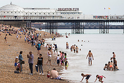© Licensed to London News Pictures. 14/08/2016. Brighton, UK. Members of the public take advantage of the few rays of sunshine as clouds hang over Brighton and the South Coast. Photo credit: Hugo Michiels/LNP