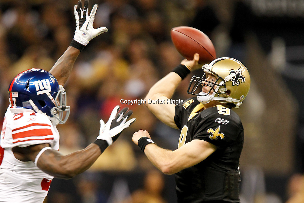 November 28, 2011; New Orleans, LA, USA; New Orleans Saints quarterback Drew Brees (9) throws under pressure from New York Giants linebacker Jacquian Williams (57)  the New York Giants during the second quarter of a game at the Mercedes-Benz Superdome. Mandatory Credit: Derick E. Hingle-US PRESSWIRE
