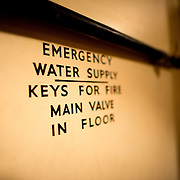 Emergency water supply sign painted on the wall at the Churchill War Rooms in London. The museum, one of five branches of the Imerial War Museums, preserves the World War II underground command bunker used by British Prime Minister Winston Churchill. Its cramped quarters were constructed from a converting a storage basement in the Treasury Building in Whitehall, London. Being underground, and under an unusually sturdy building, the Cabinet War Rooms were afforded some protection from the bombs falling above during the Blitz.