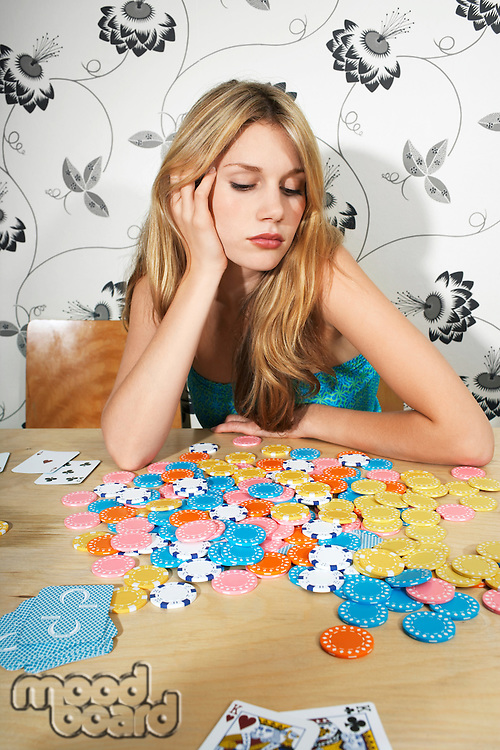 Woman Sitting at Table with Chips and Playing Cards