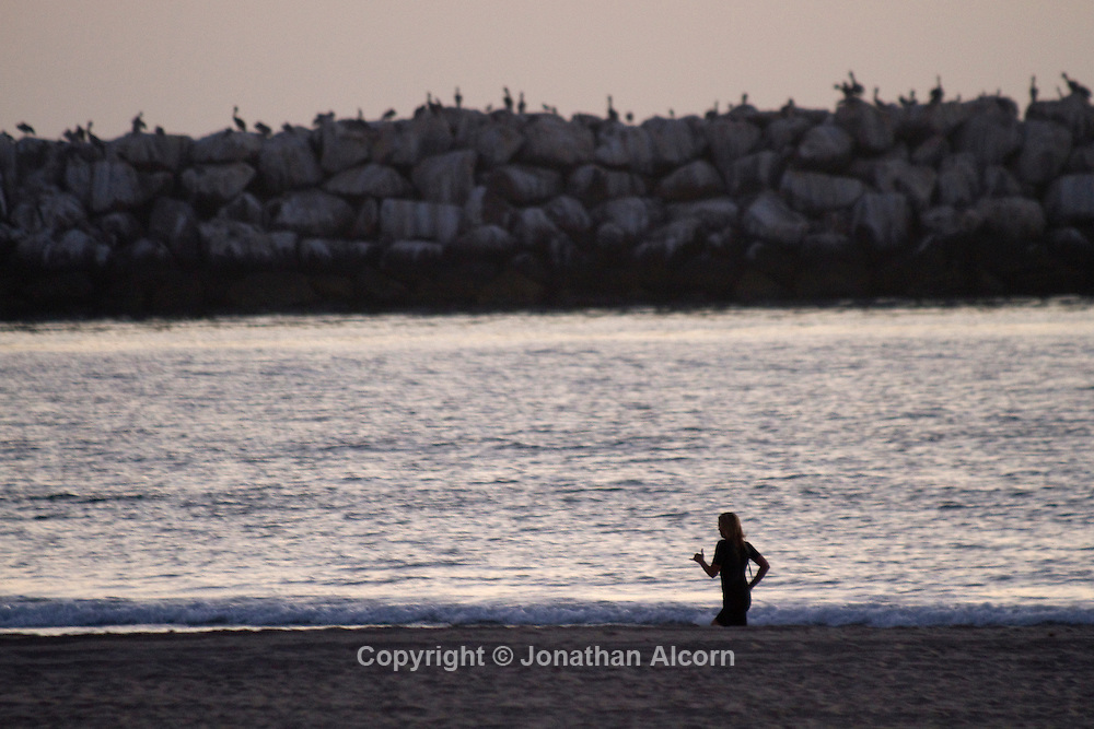 Running along Venice Beach with the outer breakwater wall of Marina del Rey in the background.