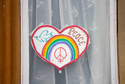 Edinburgh, Scotland, UK. 31 March, 2020. Despite Coronavirus lockdown members of the public are outside exercising and relaxing on Portobello promenade in Edinburgh. Heart and rainbow drawing in apartment window. Iain Masterton/Alamy Live News