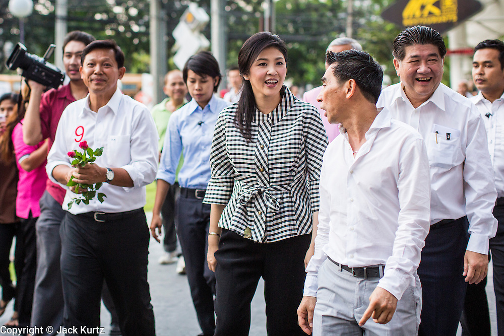 27 FEBRUARY 2013 - BANGKOK, THAILAND:  Pol Gen PONGSAPAT PONGCHAREON (left) and YINGLUCK SHINAWATRA, Prime Minister of Thailand, walk along Th. Ratchadaphisek while they campaign for Pongsapat's election to Governor of Bangkok. Police General Pongsapat Pongcharoen (retired), a former deputy national police chief who also served as secretary-general of the Narcotics Control Board is the Pheu Thai Party candidate in the upcoming Bangkok governor's election. (He resigned from the police force to run for Governor.) Former Prime Minister Thaksin Shinawatra reportedly personally recruited Pongsapat. Most of Thailand's reputable polls have reported that Pongsapat is leading in the race and likely to defeat Sukhumbhand Paribatra, the Thai Democrats' candidate and incumbent. The loss of Bangkok would be a serious blow to the Democrats, whose base is the Bangkok area.    PHOTO BY JACK KURTZ