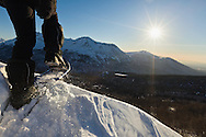 A man on snowshoes hikes over a ridge overlooking the Anchorage bowl along Arctic Valley Road in the Chugach Mountains of Chugach State Park in Southcentral Alaska in late afternoon winter sun. MR.