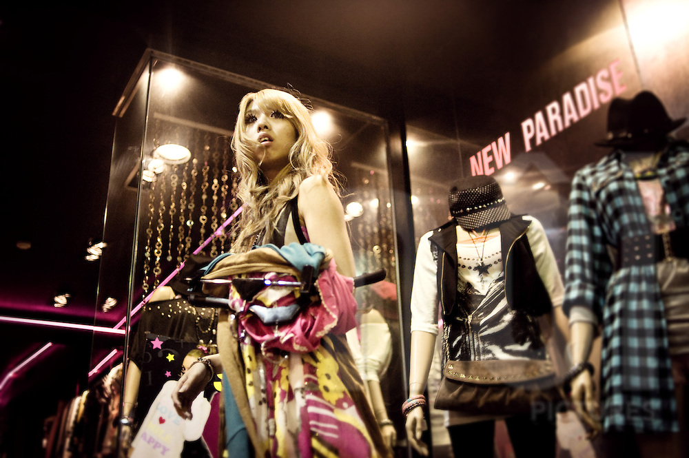 Girl leaves a changing room after trying on a variety of clothes in a shop in Taipei, Taiwan, Asia