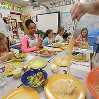 Students look on and wait as their plates are filled with a lunch they cooked at this weeks cooking camp at Parkway Elementary School.