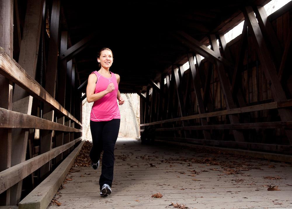 A young woman jogs through a covered bridge in Philadelphia, Pennsylvania.