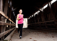 A young woman jogs through a covered bridge in Philadelphia, Pennsylvania.